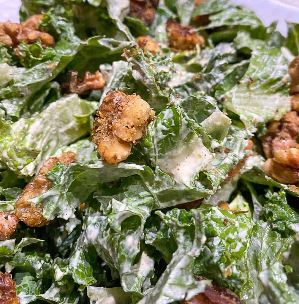 Close up of kale romain Caesar salad with walnut croutons.