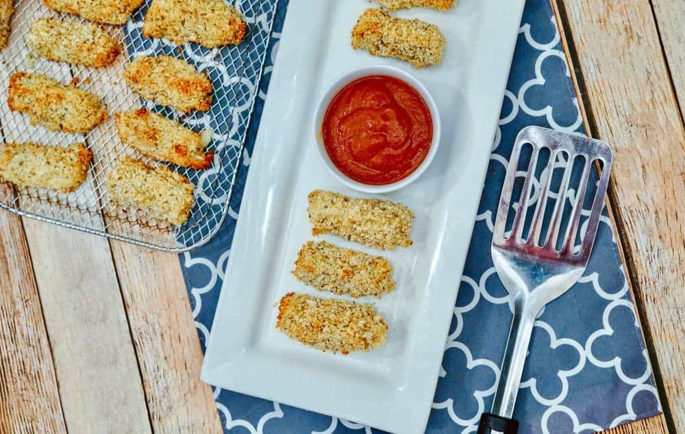 Mozzarella cheese sticks on a white platter.