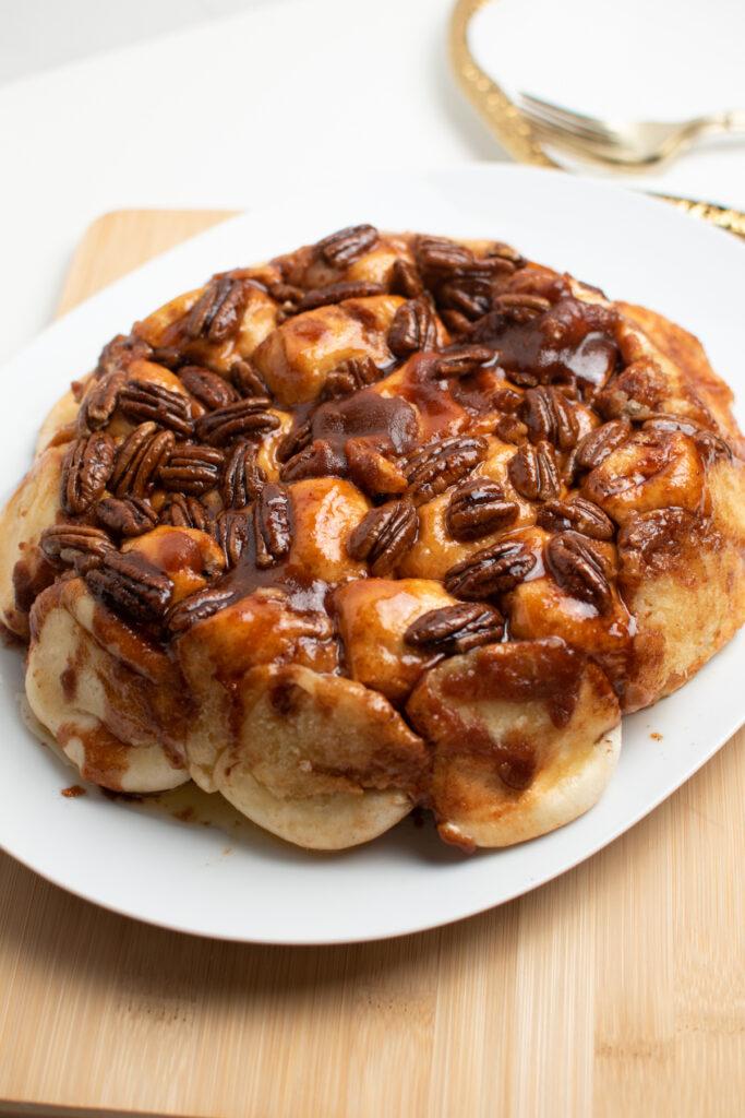 Pecan sticky buns on white platter.