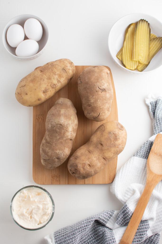 Potato salad ingredients on white table.