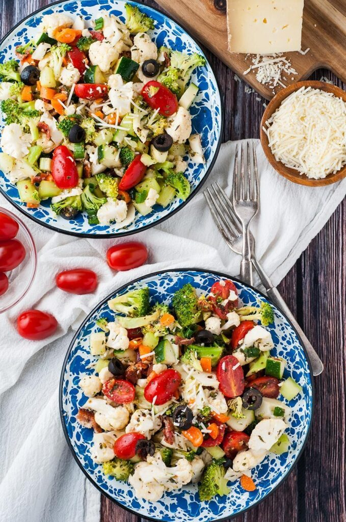 Two plates filled with vegetable salad on table.