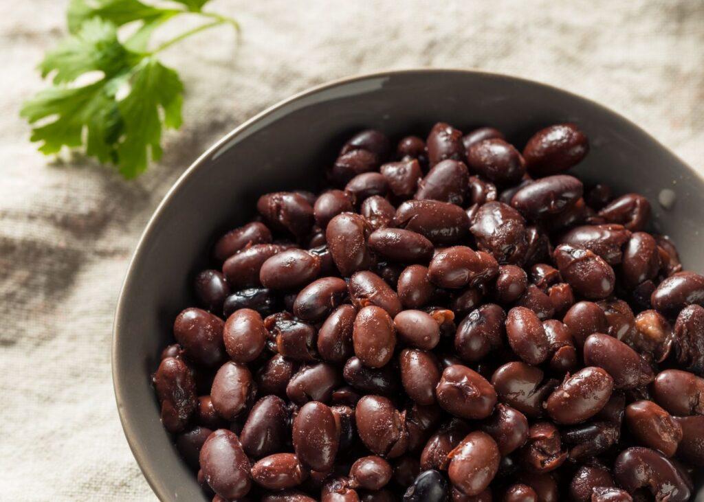 Beans in bowl next to garnish.