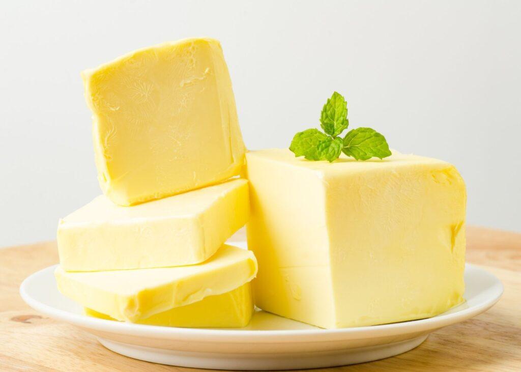 Butter sliced on white plate.