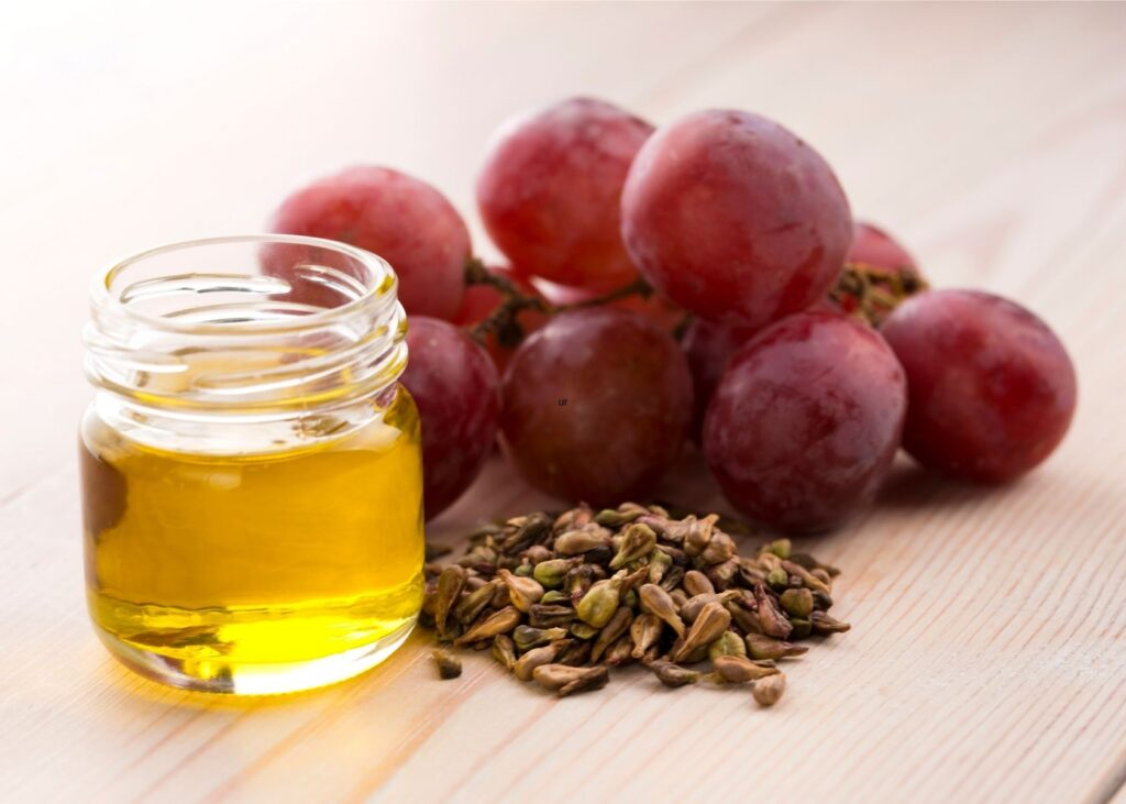 Grapes and grape seeds next to glass jar of grapeseed oil.