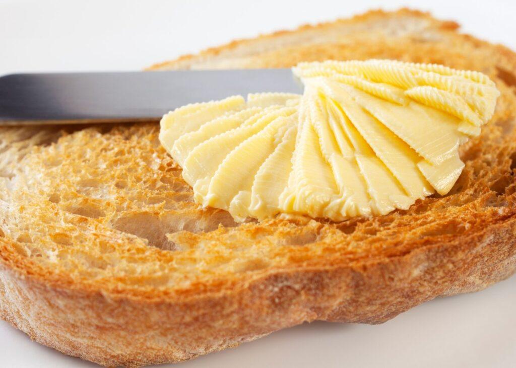 Margarine is spread on toasted bread.