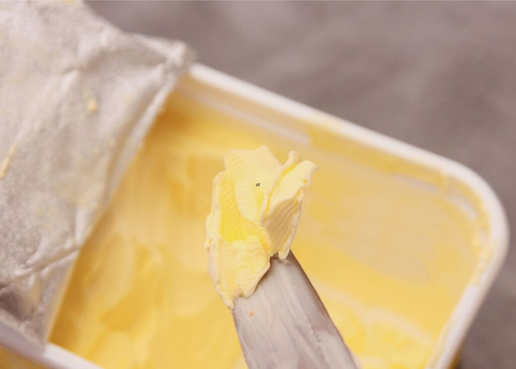 Butter knife lifts margarine out of tub.