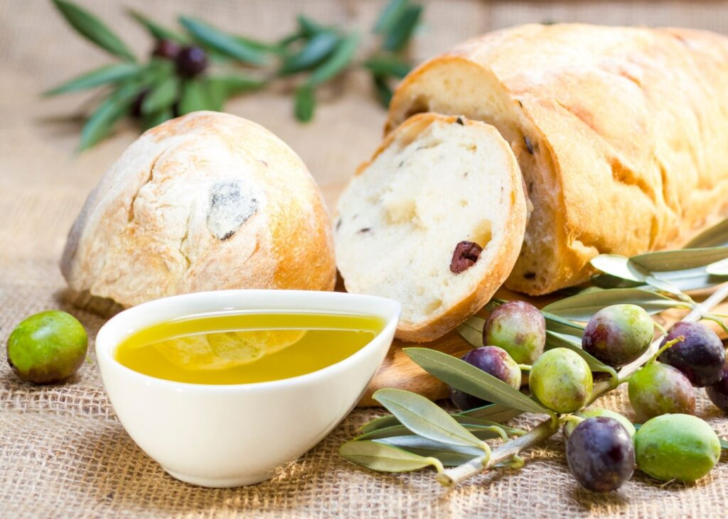Olive oil next to bread with whole olives.