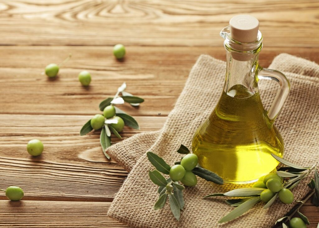 Olives and leaves next to jar of olive oil.