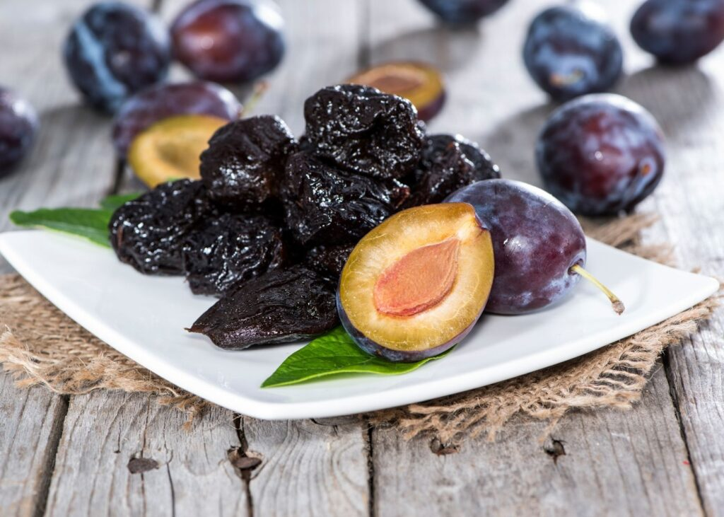 Prunes on white plate on rustic table.
