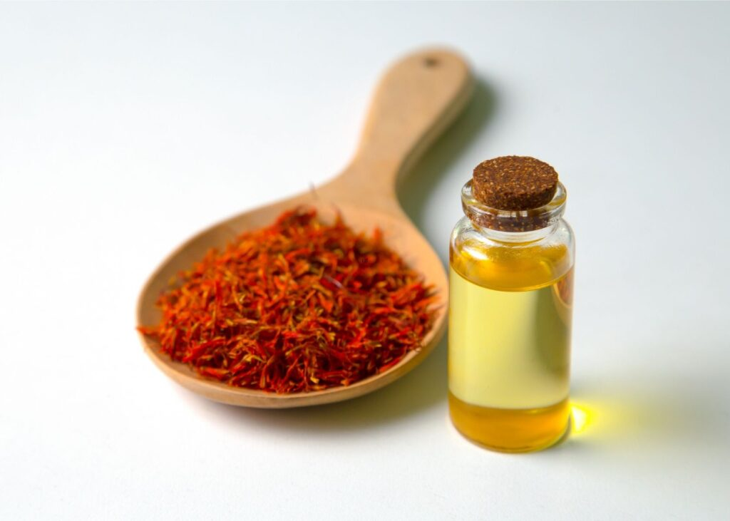 Safflower oil vegetable oil substitute in small glass jar next to wooden spoon for fronds.