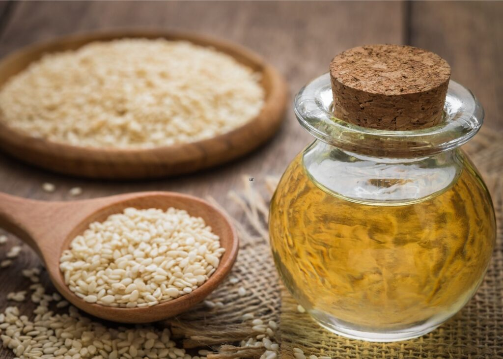 Sesame oil substitute for vegetable oil in glass jar next to bowls of sesame seeds.