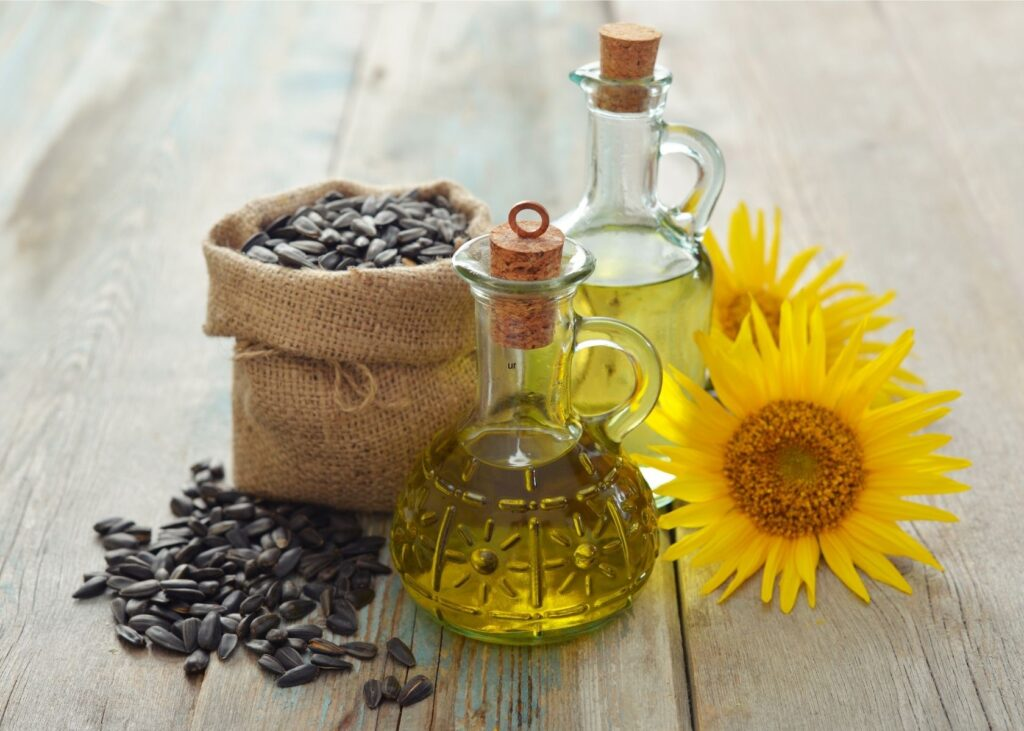 Sunflower oil in glass jars next to sunflower and bag of seeds.
