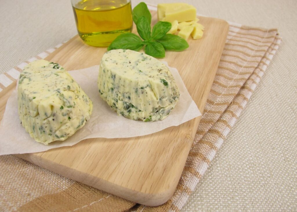 Vegan butter with herbs on wooden cutting board.