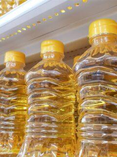 Several bottles of vegetable oil on store shelves.