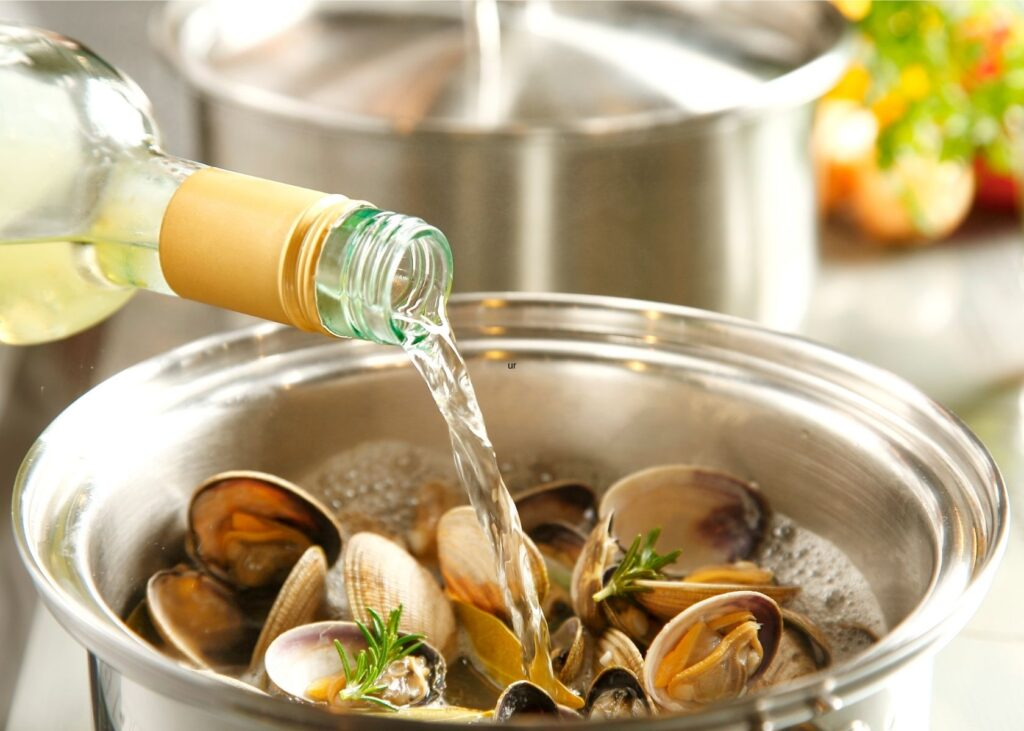 White wine substitute for chicken broth is poured into pot of clams.