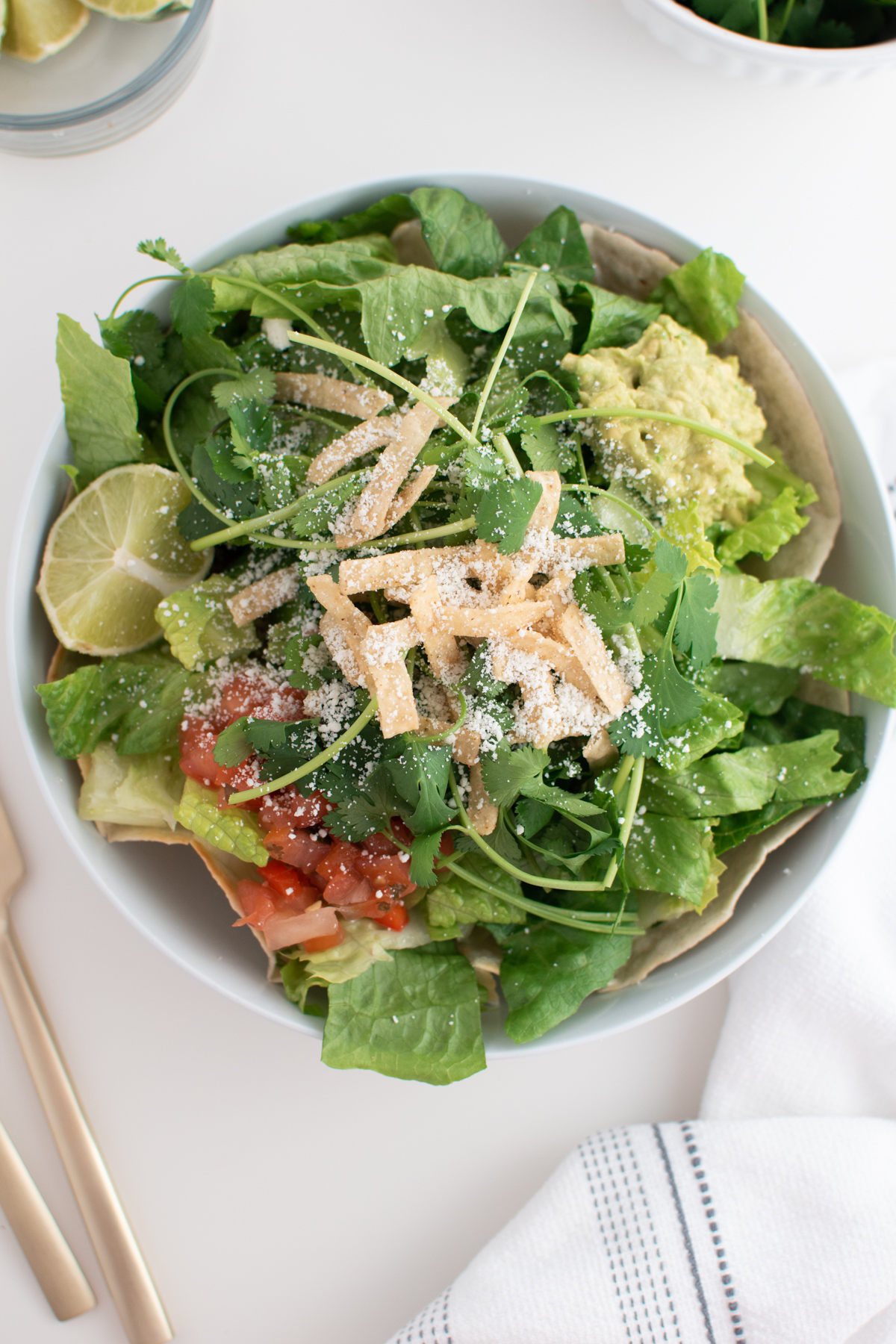 Cafe Rio chicken salad in white bowl with lettuce, tortilla strips, pico, guacamole, and creamy dressing on white table.