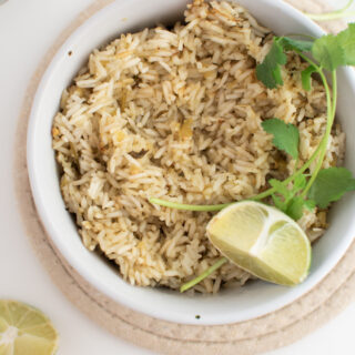 Cafe Rio rice in white bowl with lime wedge and cilantro stem.