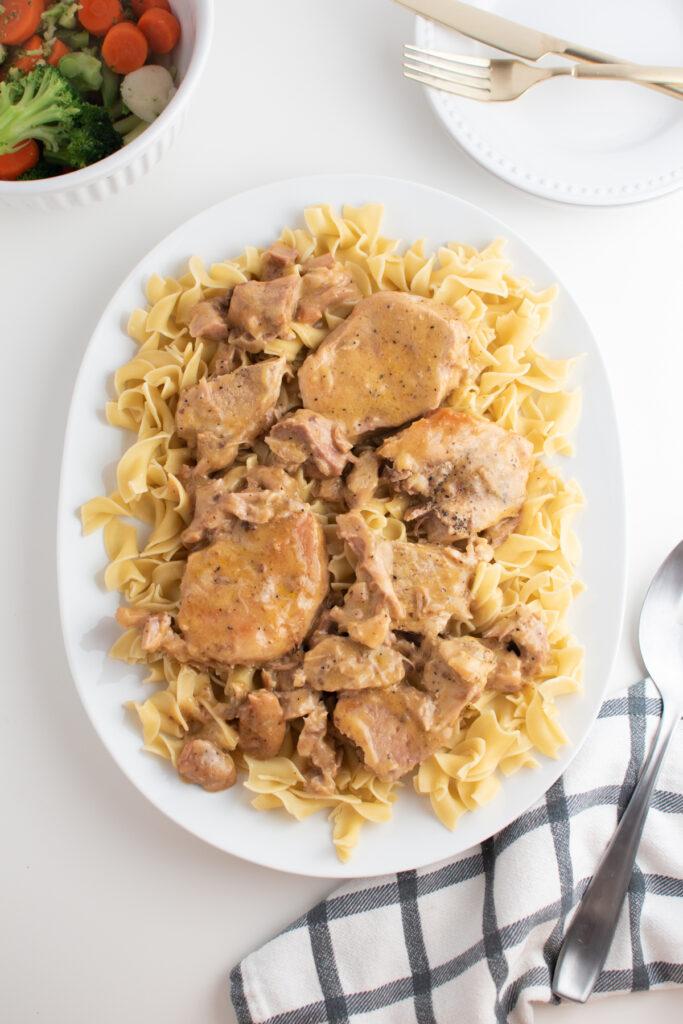 Crock Pot pork chops and egg noodles on white platter.