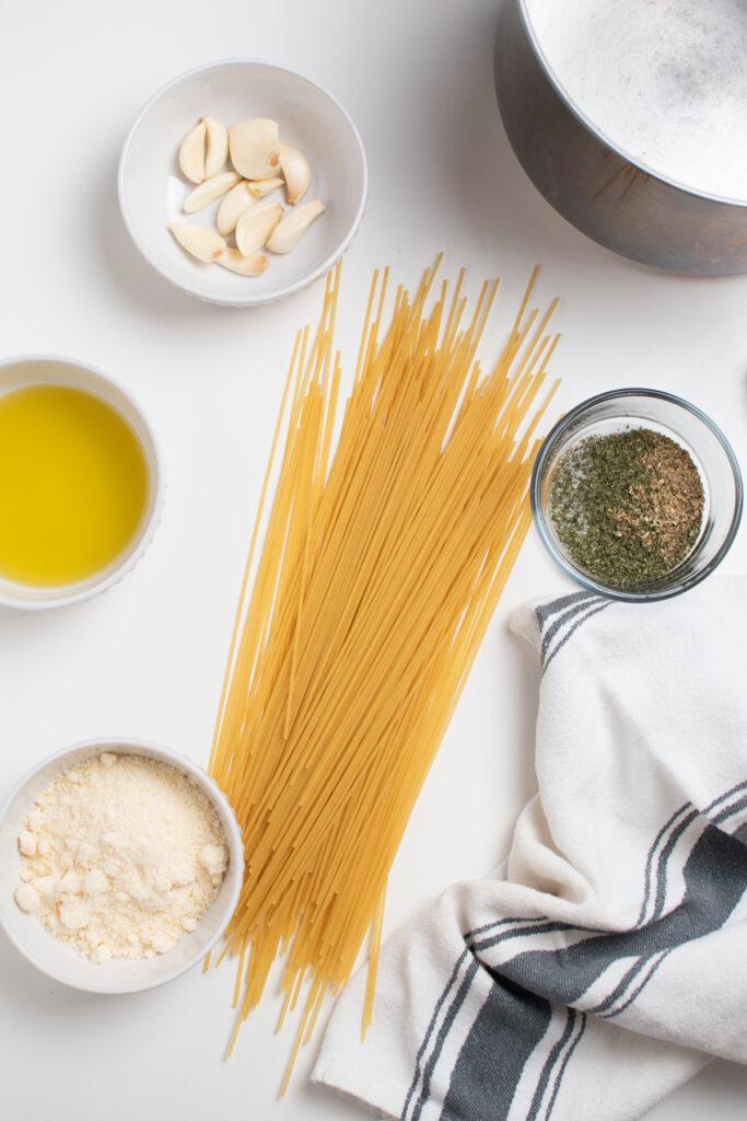 Garlic spaghetti ingredients on white table.