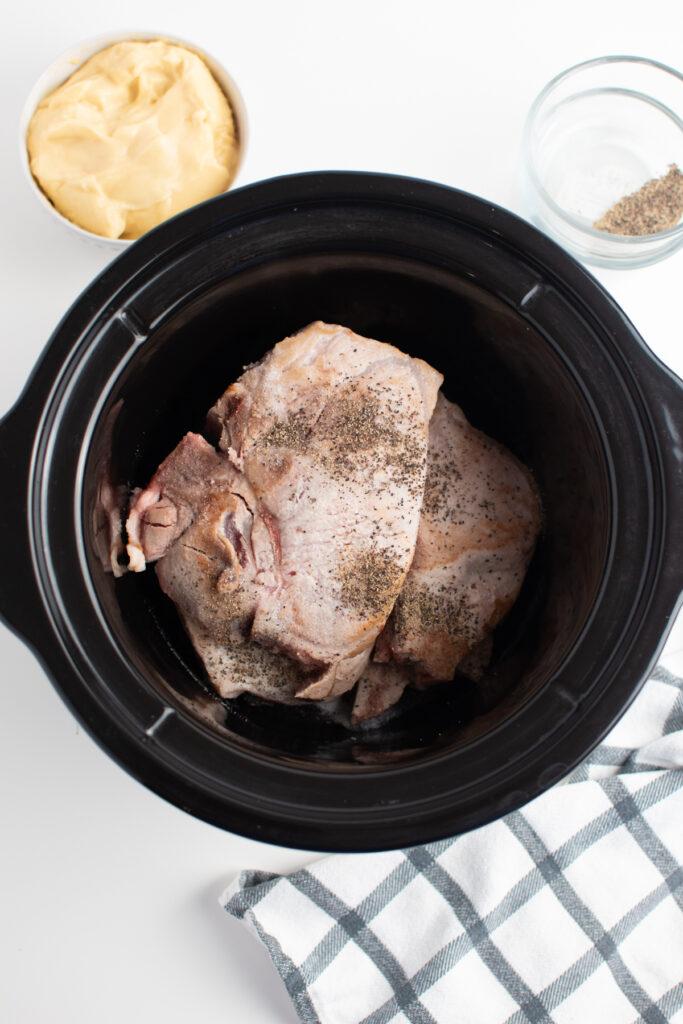 Seasoned pork chops in Crock Pot.