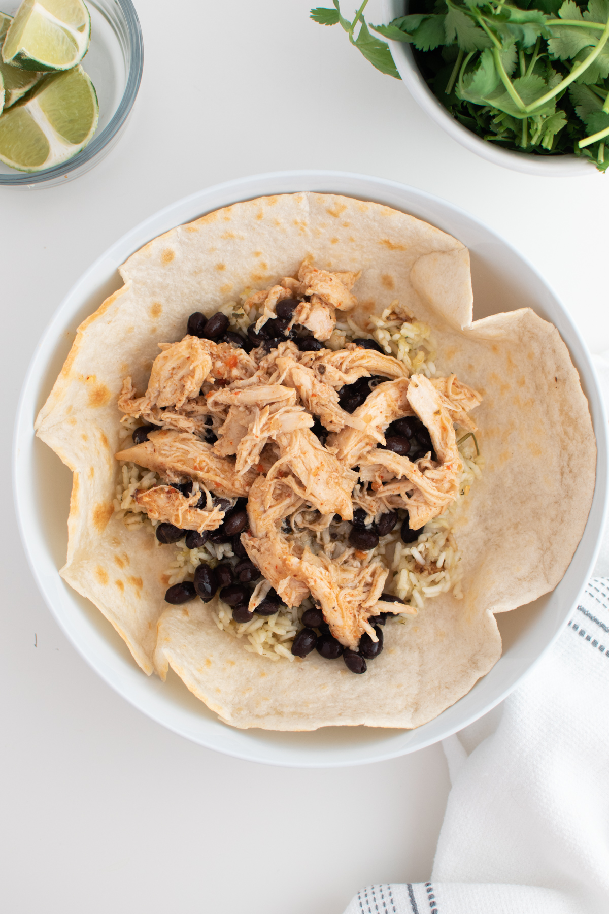 Shredded chicken, black beans, and cilantro lime rice in a tortilla all in white bowl.