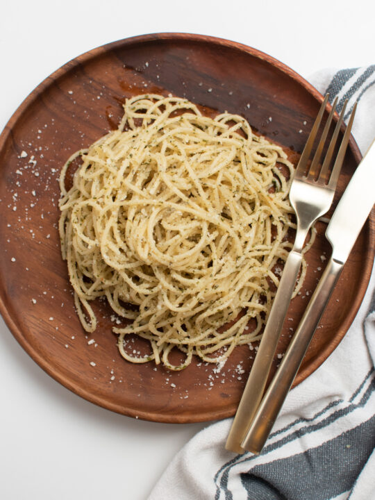 Spaghetti with olive oil and garlic on wood plate.