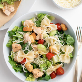 Chicken Caesar salad with pasta in white bowl next to plate of salad