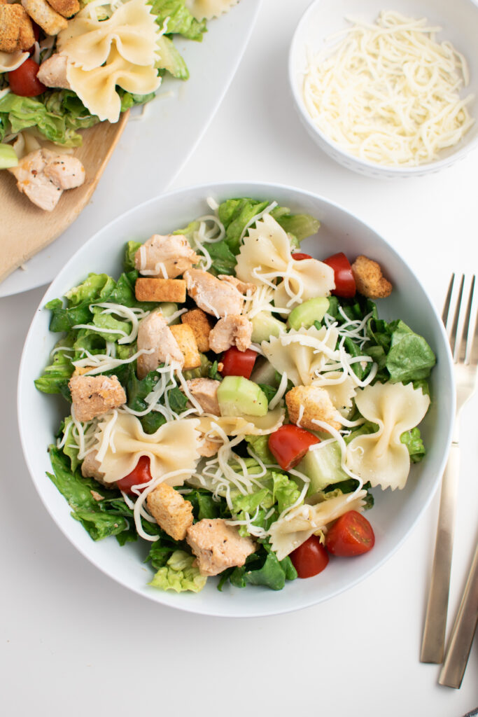Chicken Caesar salad with pasta in white bowl.