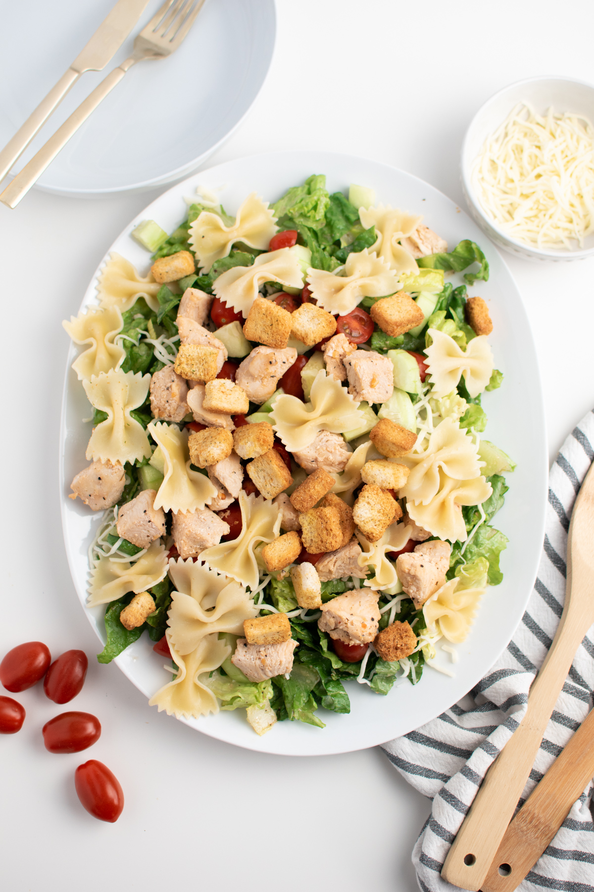 Chicken Caesar pasta salad on large white platter next to kitchen towel and wooden spoon.