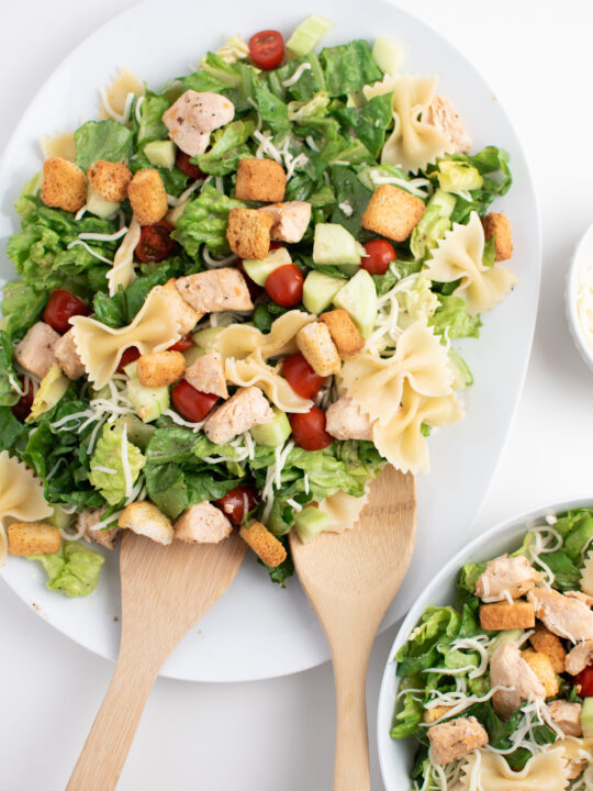Chicken Caesar salad with pasta, croutons, cheese and tomatoes on white platter.