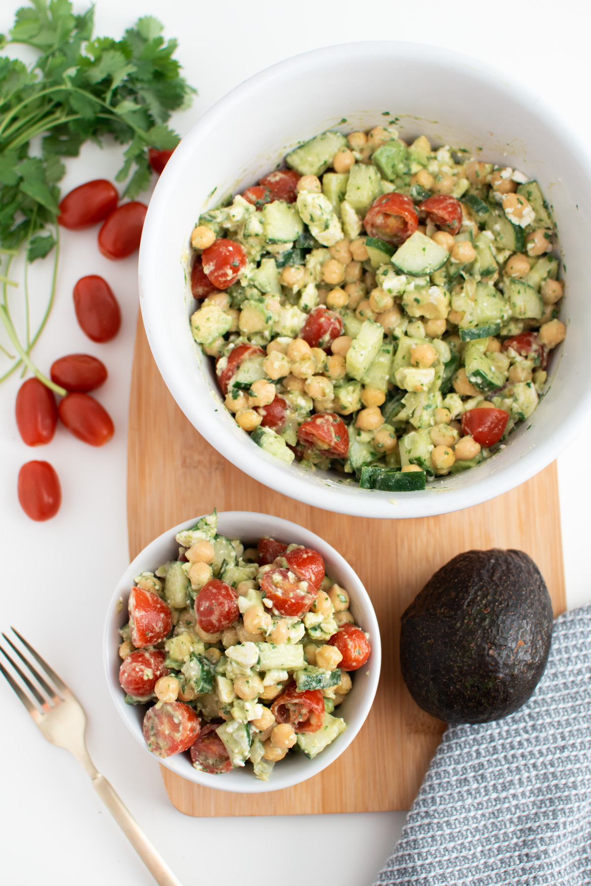Chickpea salad with cilantro and feta in white bowls on wooden cutting board.