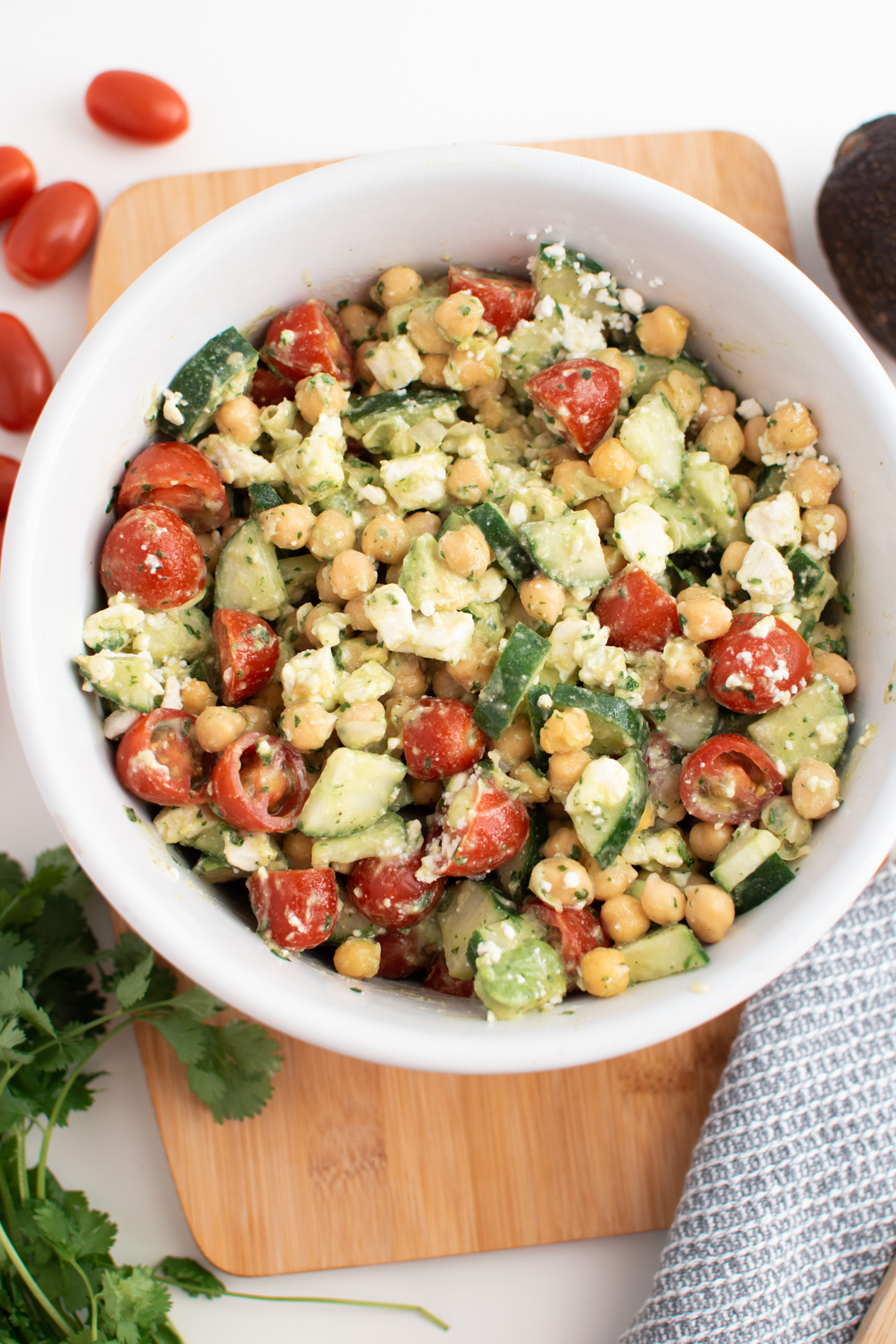 Chickpea salad with feta in white serving bowl on wooden cutting board.