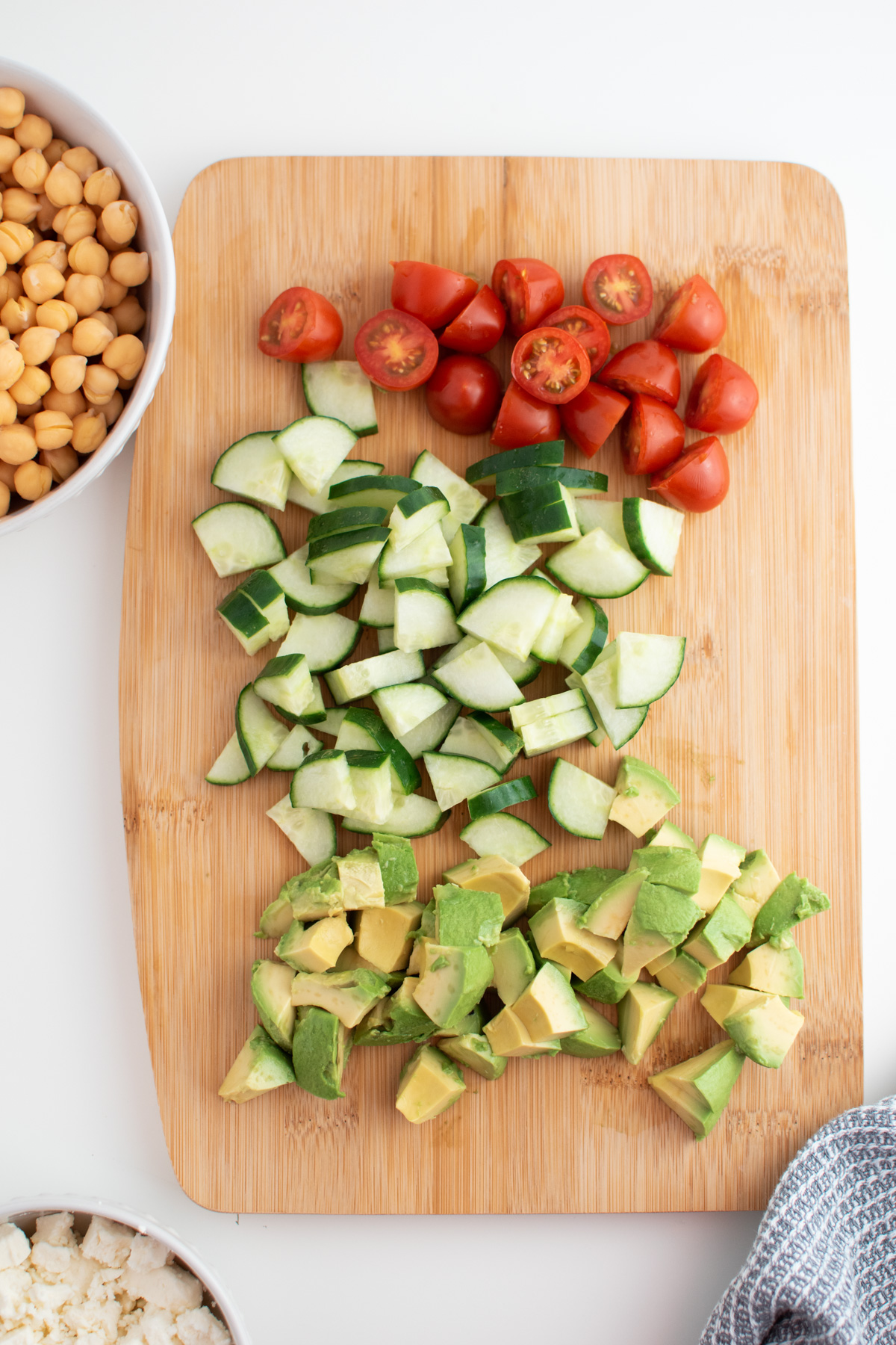 Chopped tomatoes, cucumbers, and avocado on wooden cutting board next to feta and chickpeas.