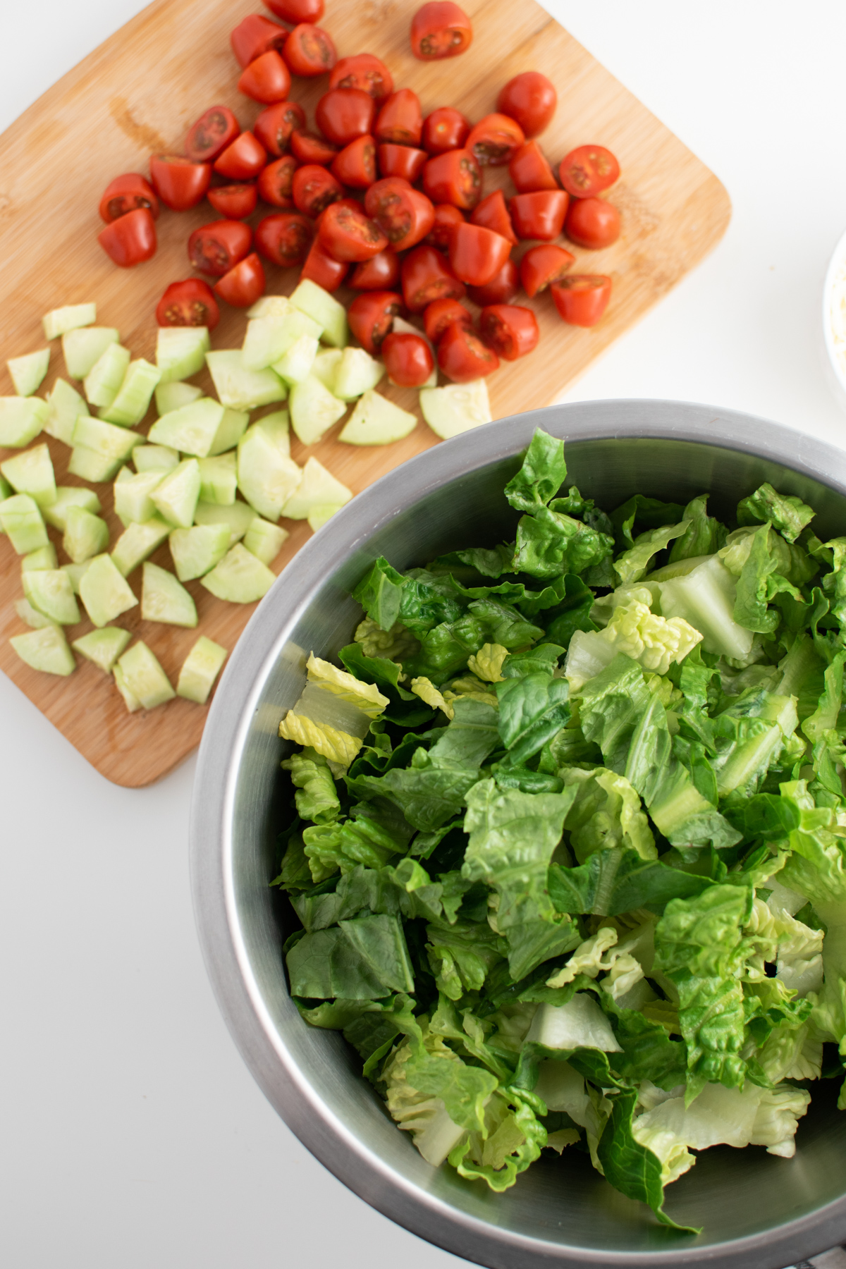 Chopped lettuce in metal mixing bowl next to chopped cucumbers and tomatoes on cutting board.