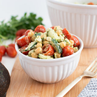 Cilantro chickpea salad in small white serving bowl next to fresh vegetables.