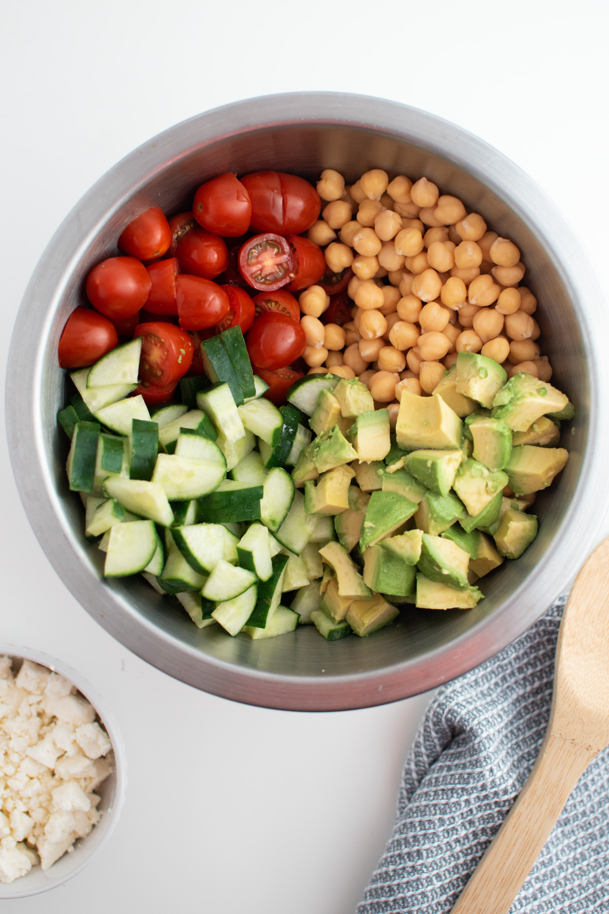 Cilantro chickpea salad ingredients in large metal mixing bowl next to bowl of feta.