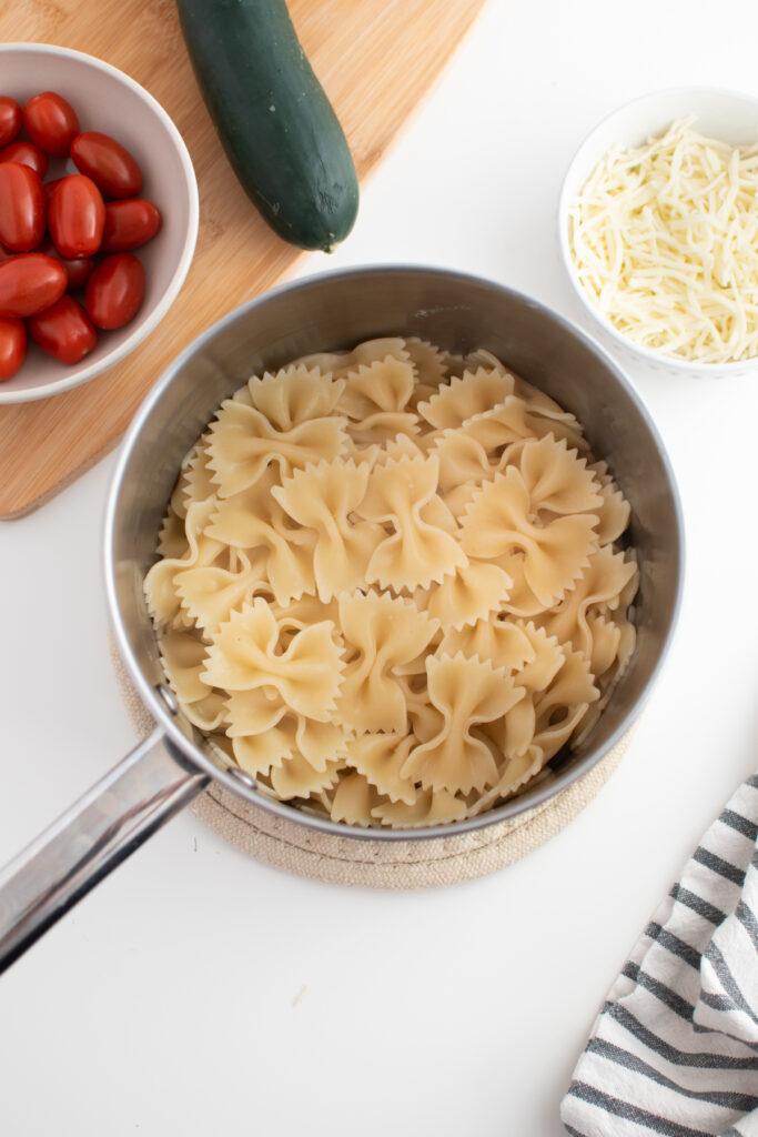 Cooked bowtie pasta in pot.