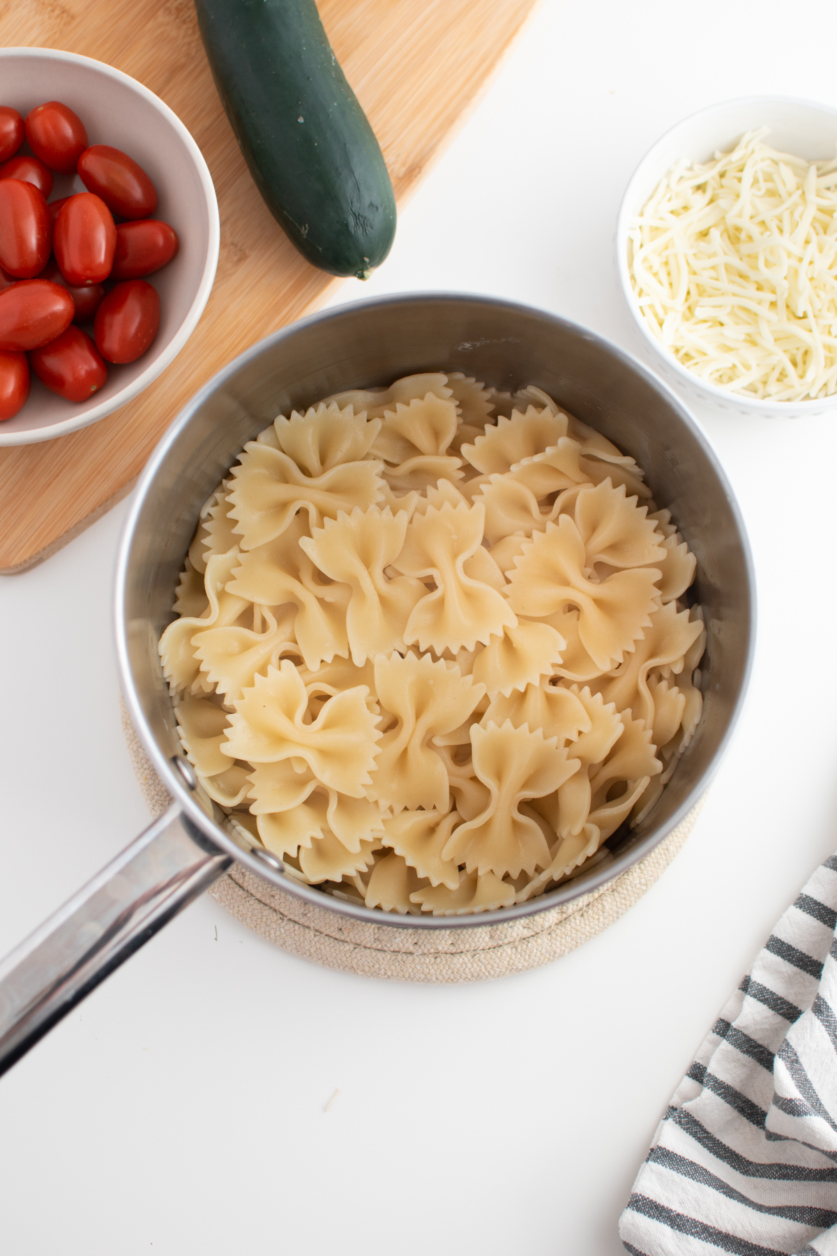 Cooked bowtie pasta in pot next to cucumber and a bowl of tomatoes and cheese.