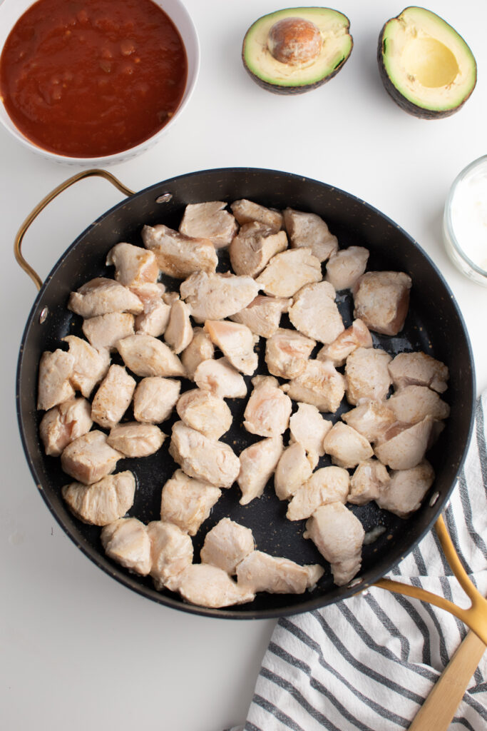Cooked chicken pieces in large skillet.