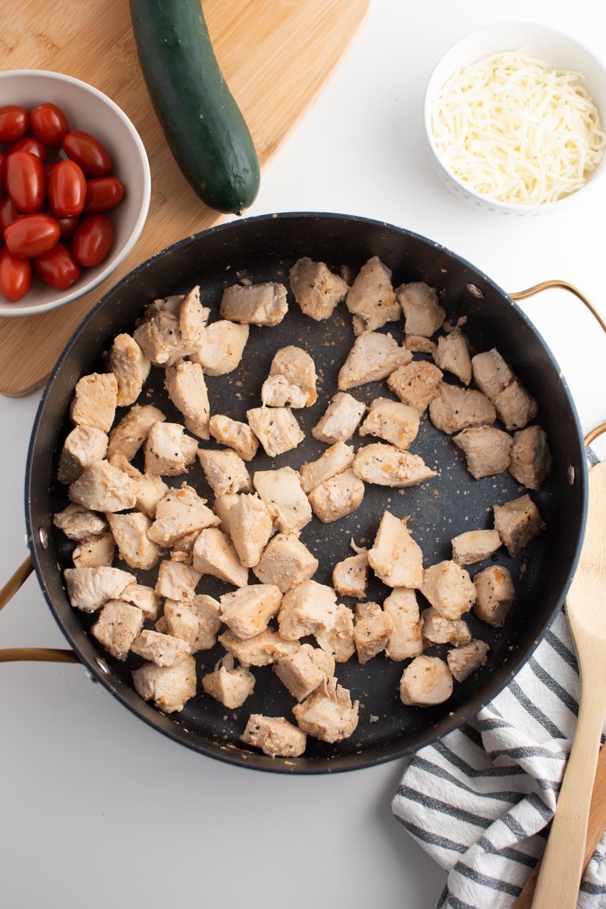 Cooked seasoned chicken in black skillet next to bowl of tomatoes and bowl of cheese.
