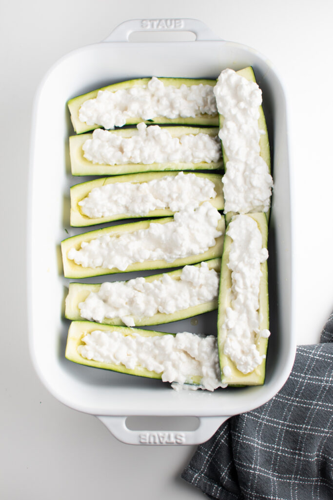 Cottage cheese filled zucchini boats in dish.