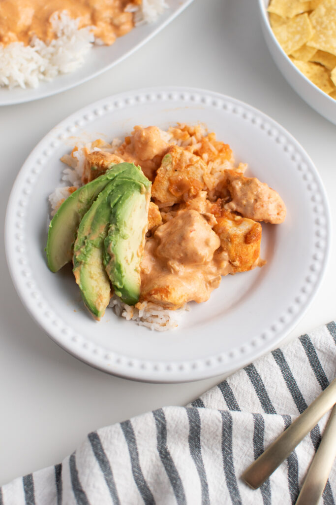 Creamy picante sauce chicken on white plate.