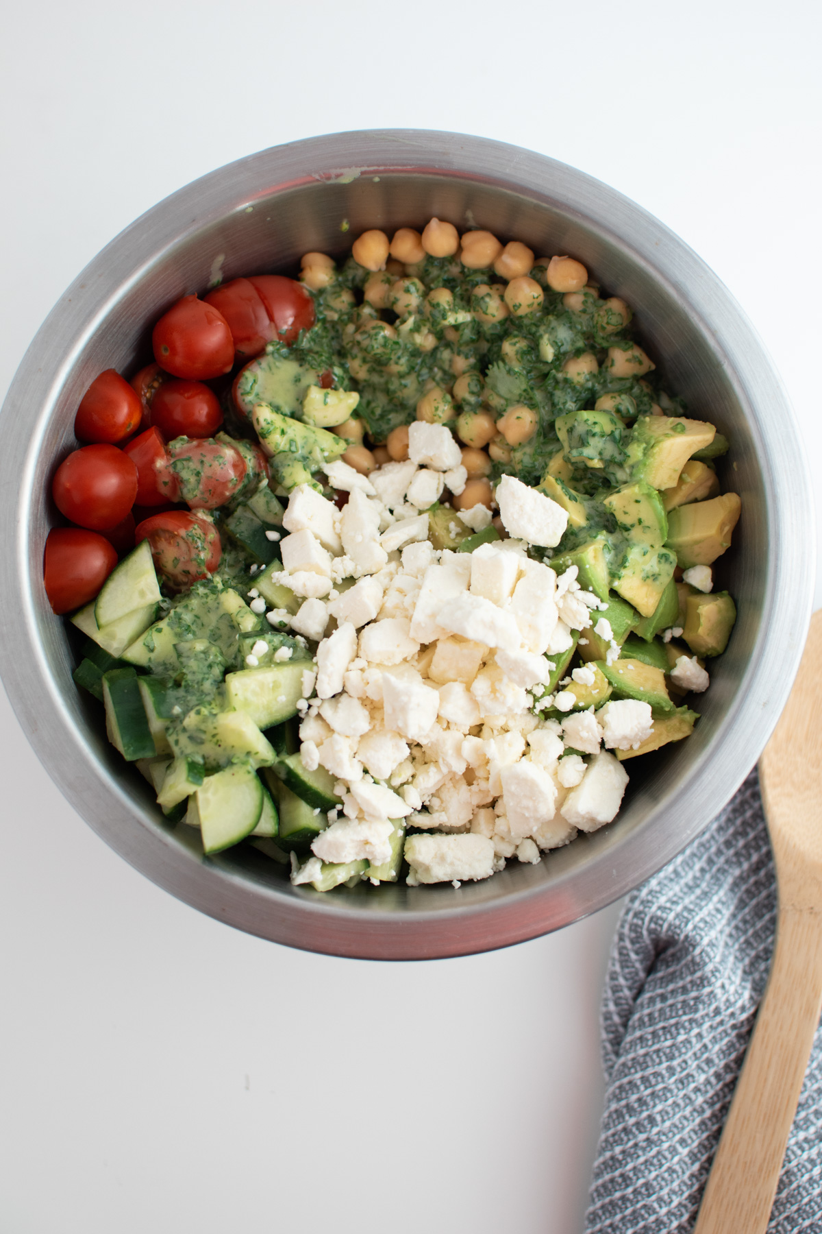 Feta cheese in chickpea salad with tomatoes, cucumber and avocado in mixing bowl.