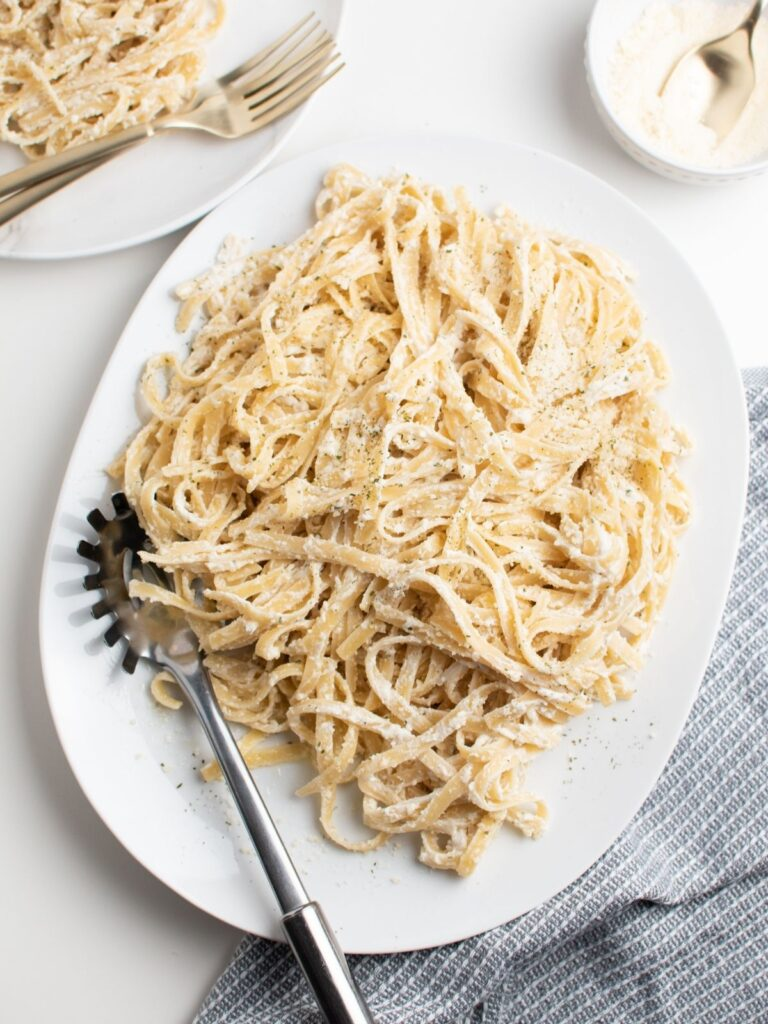 Platter with healthy fettuccine alfredo and pasta spoon.