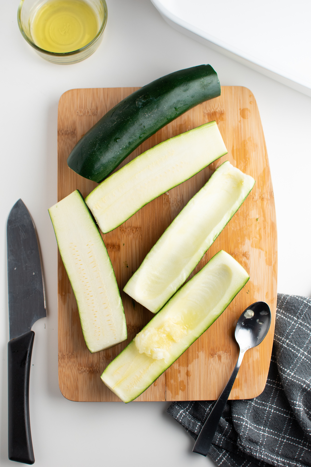 Hollowed out zucchini boats on cutting board next to knife and spoon.