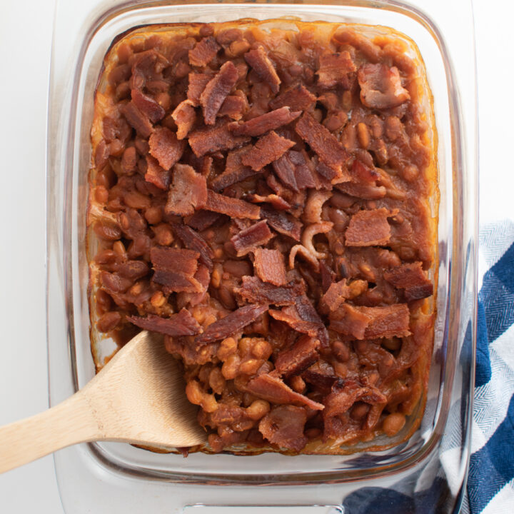Homemade baked beans in glass dish.