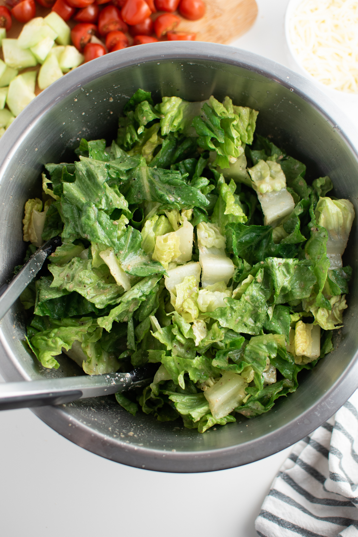 Lettuce with Caesar dressing in large metal mixing bowl with blue and white kitchen towel.