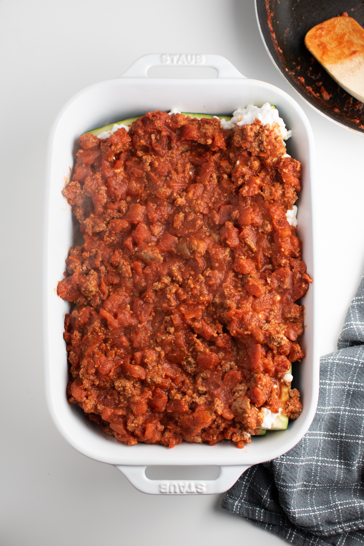Lasagna meat sauce covering zucchini boats in white baking dish.