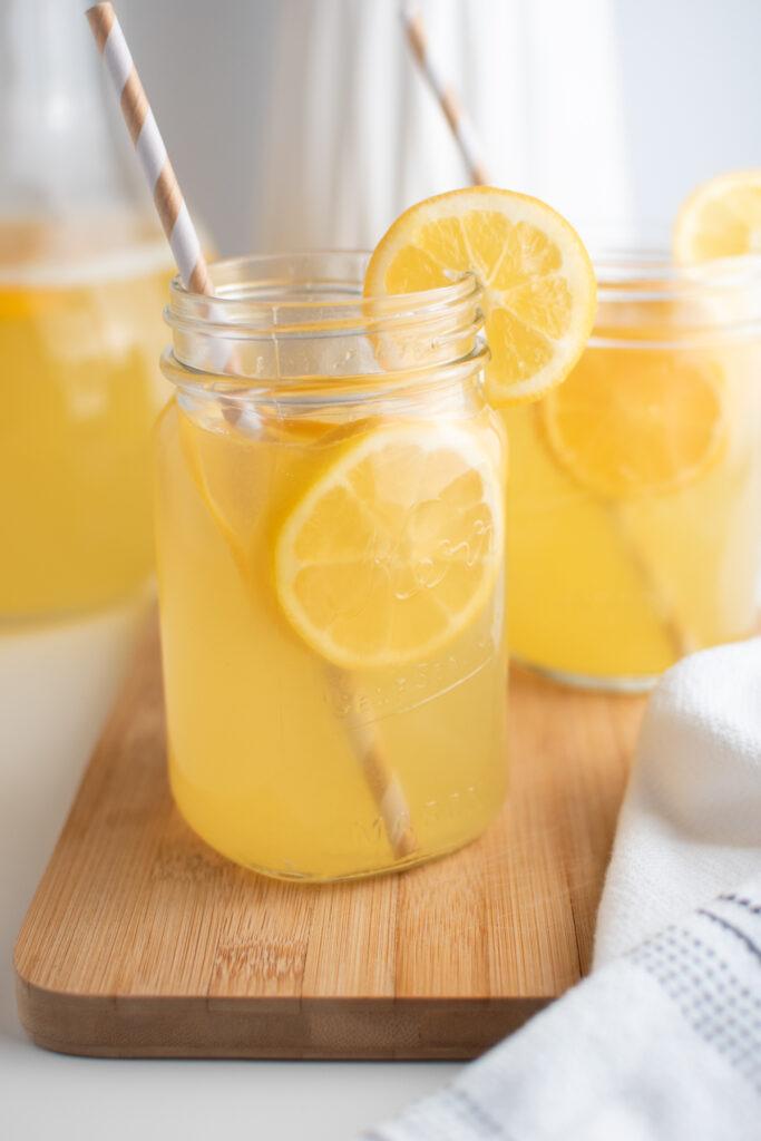 Glass cups of Meyer lemon lemonade on wood board.