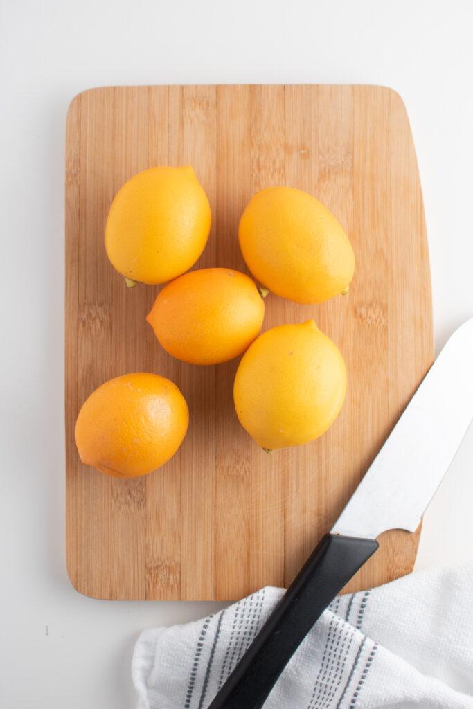 Meyer lemons on wood cutting board.